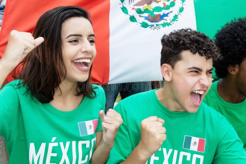 Aficionados al fútbol jovenes de México con la bandera mexicana fotografía de archivo