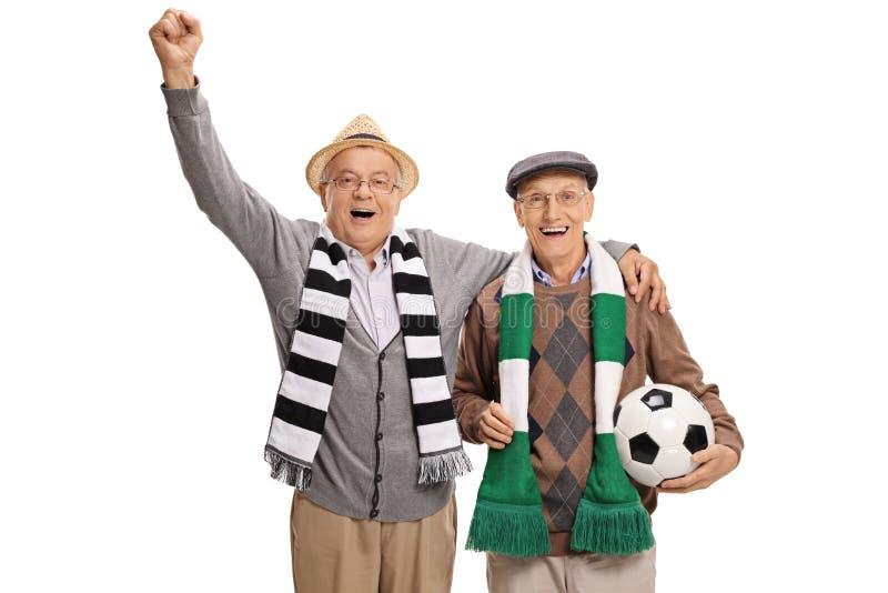Aficionados al fútbol maduros extáticos con bufandas y animar del fútbol imagen de archivo