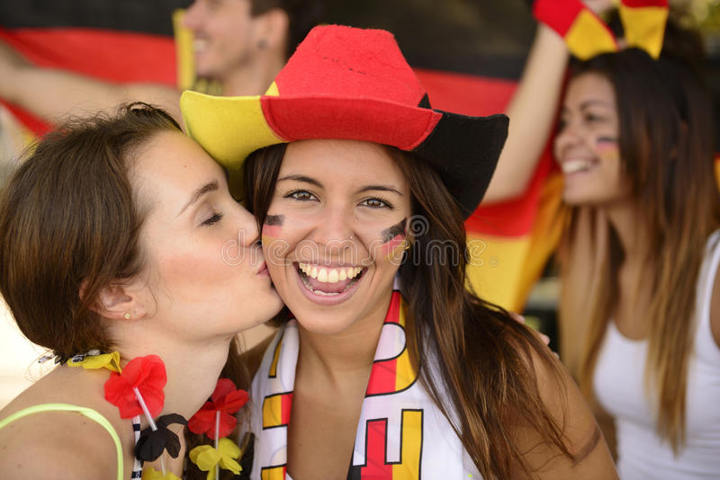 Aficionados deportivos alemanes del fútbol que besan la celebración. imagenes de archivo