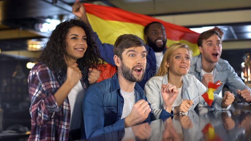 Aficionados deportivos con la bandera espa?ola que disfruta del torneo, celebrando el juego que gana fotografía de archivo libre de regalías