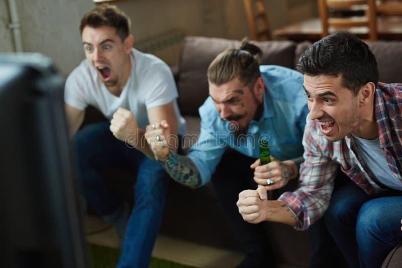 Aficionados deportivos emocionados que animan para la TV imágenes de archivo libres de regalías