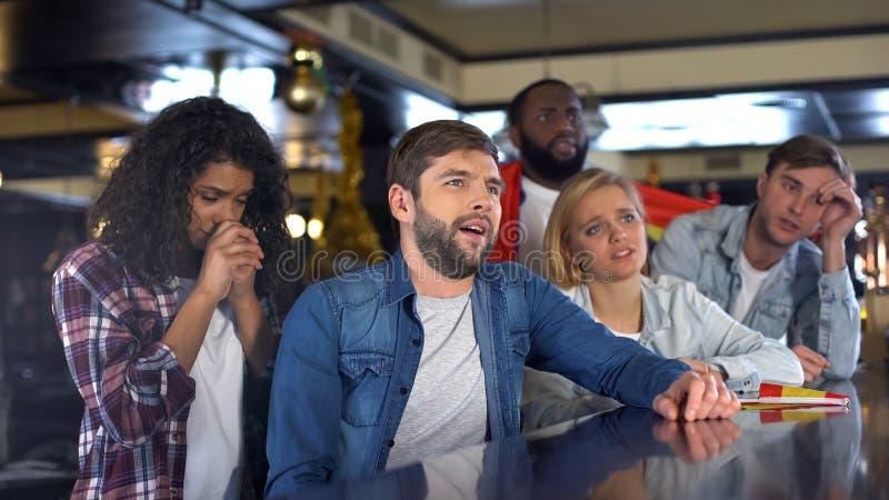 Aficionados deportivos multiétnicos que apoyan al equipo nacional en el pub, trastorno sobre derrota fotografía de archivo