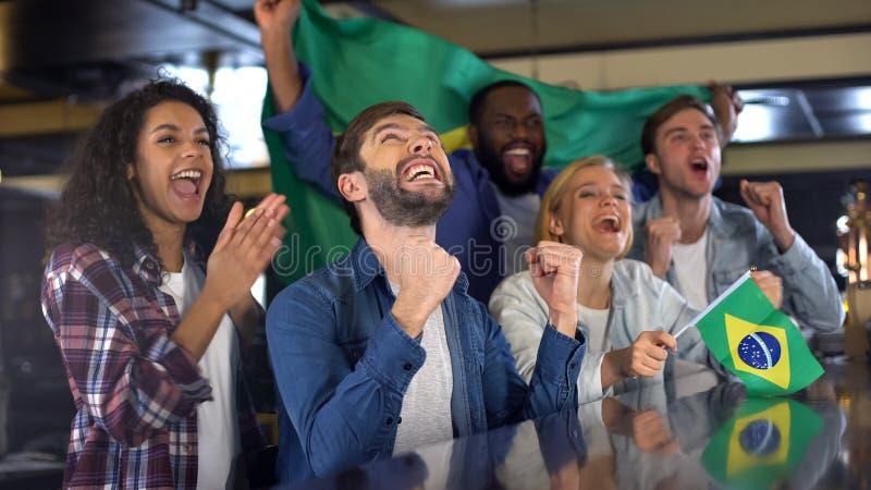 Aficionados desportivos extremamente felizes que acenam a bandeira de Brasil a favor da equipe nacional imagem de stock