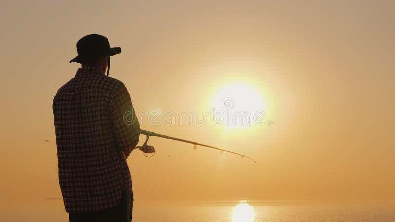 Aficiones y actividades - un hombre joven está pescando en la playa en la puesta del sol fotos de archivo