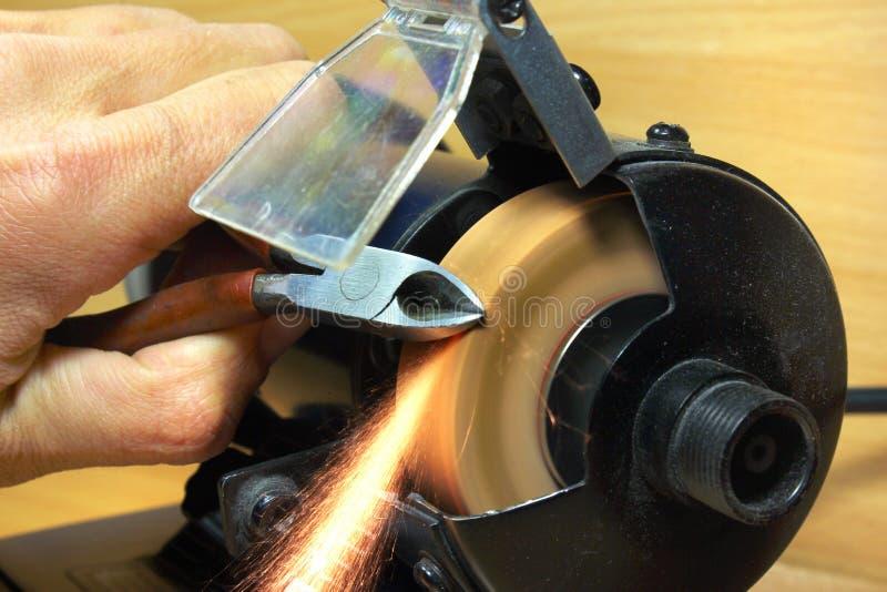 Afiladura de los alicates laterales del corte en la muela abrasiva eléctrica imagen de archivo