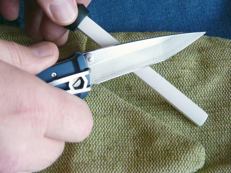 Afiladura de un cuchillo en un musat de cerámica imagenes de archivo