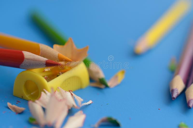 Afile los lápices coloreados con sacapuntas foto de archivo