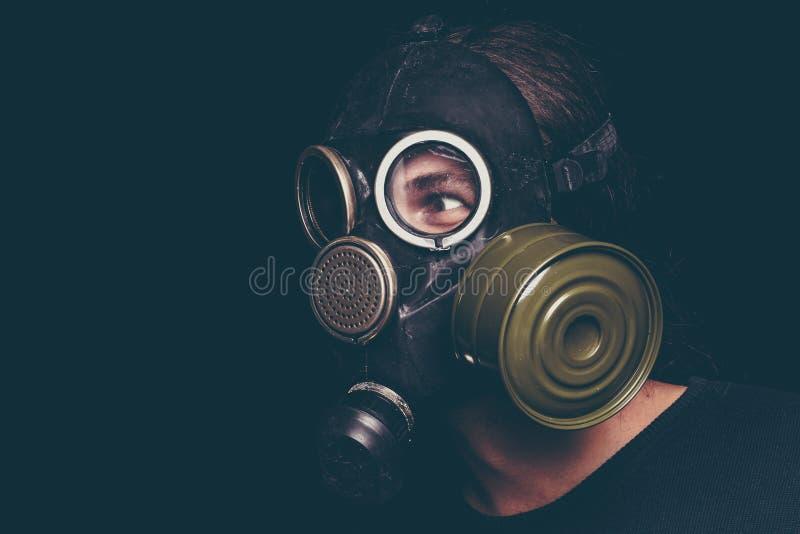 Afixe o homem apocalíptico do sobrevivente na máscara de gás no fundo preto, olhos assustadores imagens de stock