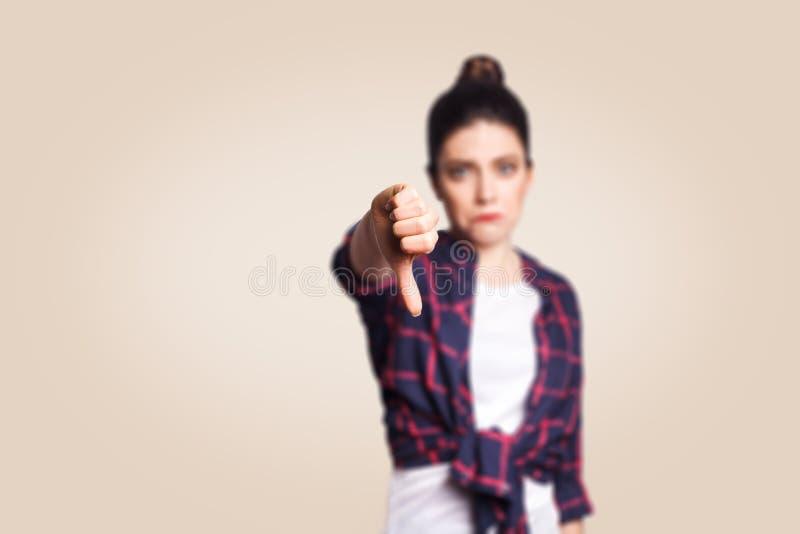 afkeer Het jonge ongelukkige verstoorde meisje met toevallig stijl en broodjeshaar beduimelt onderaan haar vinger, op beige blind royalty-vrije stock afbeeldingen