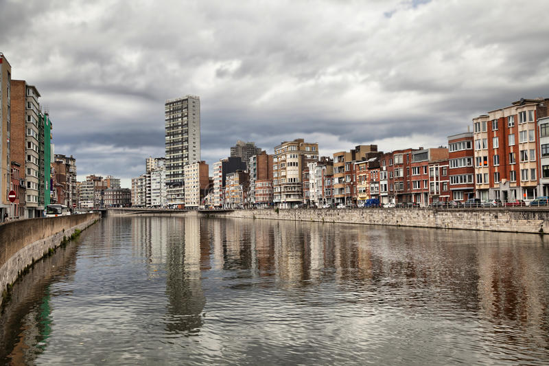 Afleiding van rivier Meuse onder bewolkte hemel in Luik stock foto's