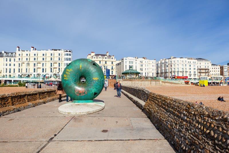 Afloat artwork on Brighton beach. Brighton, England, October 07, 2018. View of Brighton beach behing the public artwork `Afloat`, circular donut shaped globe royalty free stock image