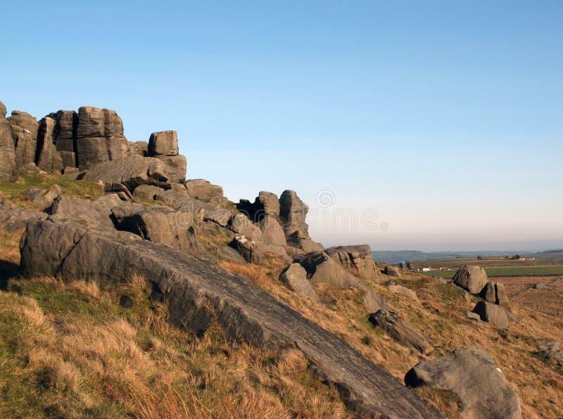 Afloramiento rugoso grande del gritstone en los bridestones una formaci?n de roca grande en West Yorkshire cerca del cielo azul d imágenes de archivo libres de regalías