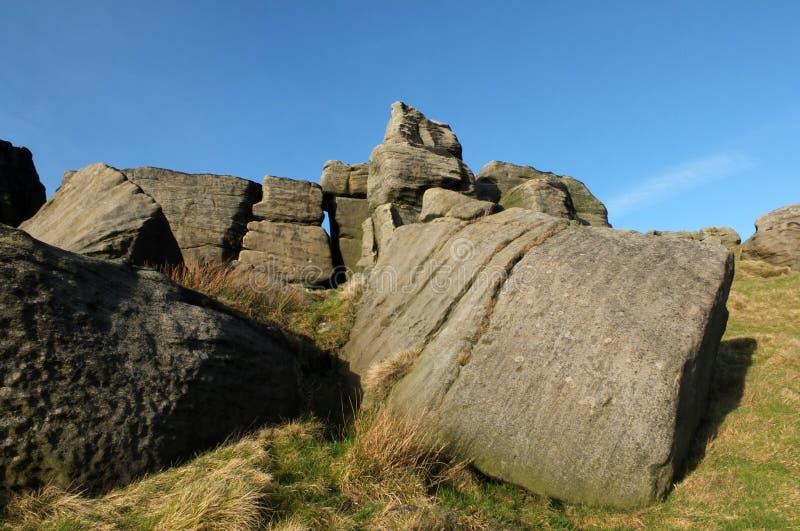 Afloramiento rugoso grande del gritstone en los bridestones una formaci?n de roca grande en West Yorkshire cerca del cielo azul d fotos de archivo libres de regalías
