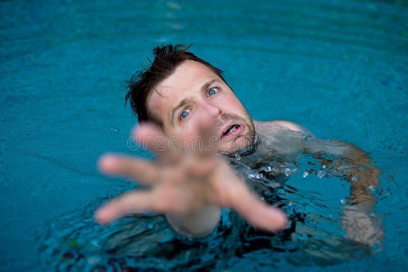 Afogando o homem caucasiano na piscina que pede a ajuda Ele que estica suas mãos no medo fotos de stock royalty free