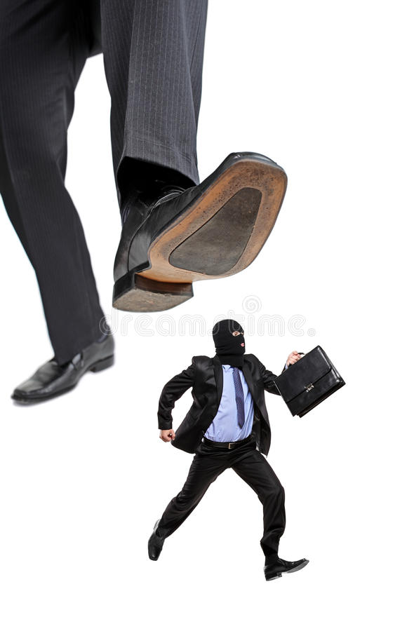 An afraid burglar running away from a big foot royalty free stock image