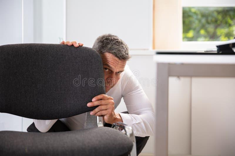Afraid Businessman Peeking Behind Chair. Afraid Mature Businessman Peeking Behind Chair In Office royalty free stock photo