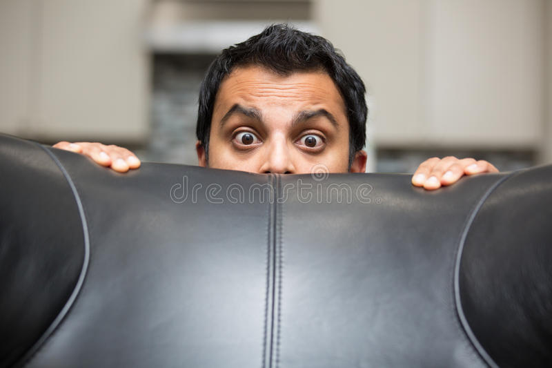 Afraid. Closeup portrait, grown young man hiding behind black leather couch, afraid and worried, isolated indoors background royalty free stock photo