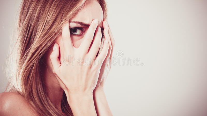 Afraid frightened woman peeking through her fingers. On grey. Shy teen girl covering face with hands royalty free stock photos