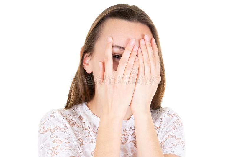 Afraid frightened young woman peeking through her fingers hands both palm. An Afraid frightened young woman peeking through her fingers hands both palm stock image