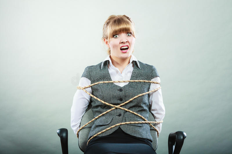 Afraid kidnapped woman tied with rope to chair. Afraid kidnapped businesswoman tied with rope to chair. Woman kept prisoner. Girl being imprisoned incarcerated royalty free stock images
