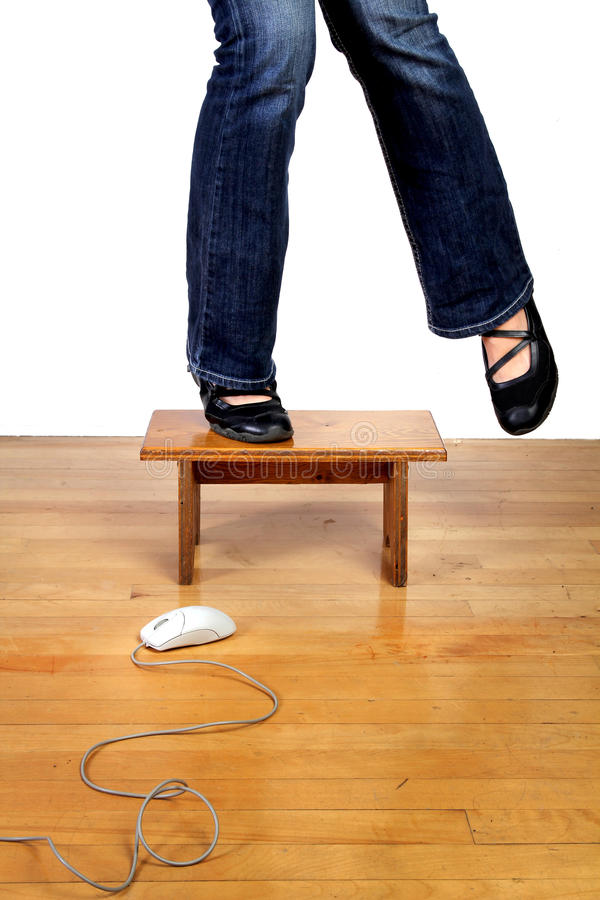 Afraid of new technology. Conceptual image of a scared technophobe woman stood on a low table to escape from a computer mouse