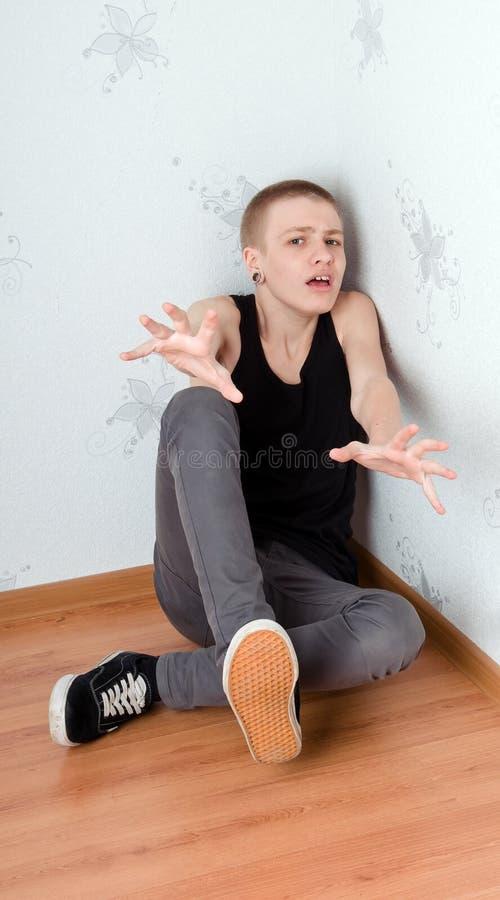 Afraid teenager. Teen afraid to sit in the corner stock photo