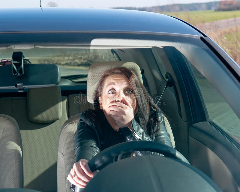 Afraid woman in the car. Afraid young woman in the car royalty free stock photography