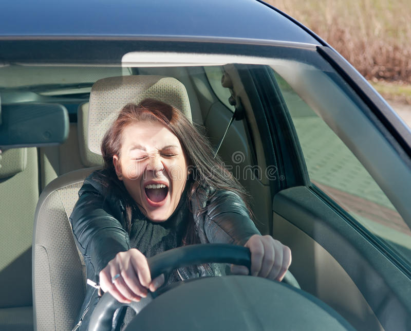 Afraid woman in the car. Afraid young woman screaming in the car royalty free stock images