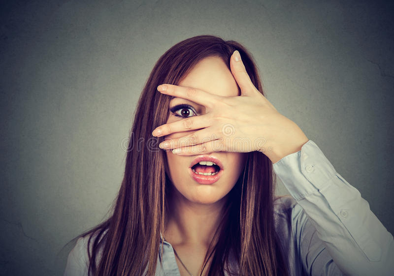 Afraid woman peeking through her fingers. Afraid young woman peeking through her fingers stock photography