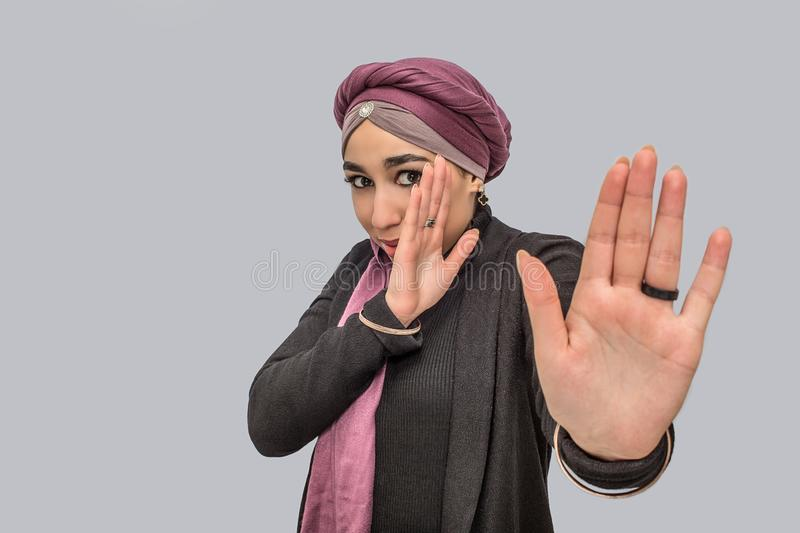 Afraid young arabian woman look at camerea. She try to cver her face with hands. She is scared. Isolated on grey. Background stock photo
