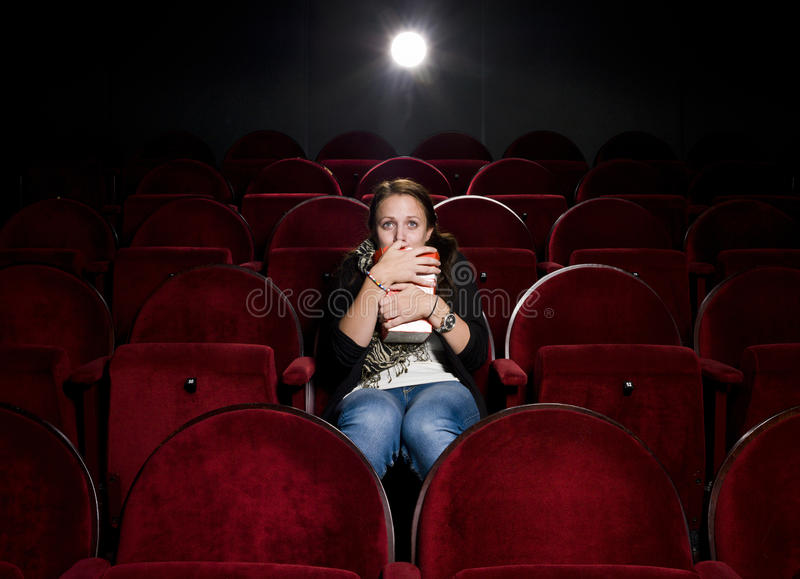 Afraid young woman. Alone in the movie theater stock photography