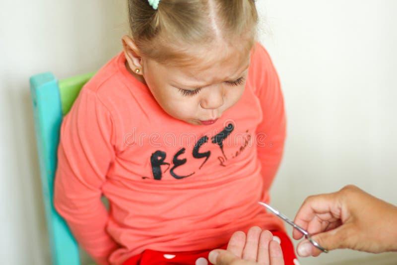 Afraiding маленькой девочки уравновешивать ногти ножницами маникюра стоковое изображение rf
