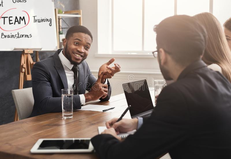 African-american applicant at job interview. Cheerful african-american applicant talking at job interview to hr comission at job interview, copy space stock photo