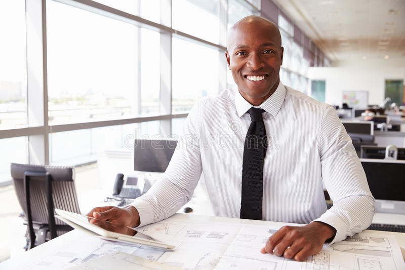 African American architect at work, smiling to camera royalty free stock photo