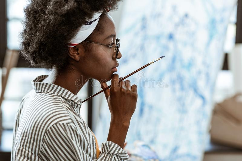 African-American artist feeling thoughtful working on new picture. Thoughtful artist. African-American artist feeling thoughtful while working on new picture in stock image