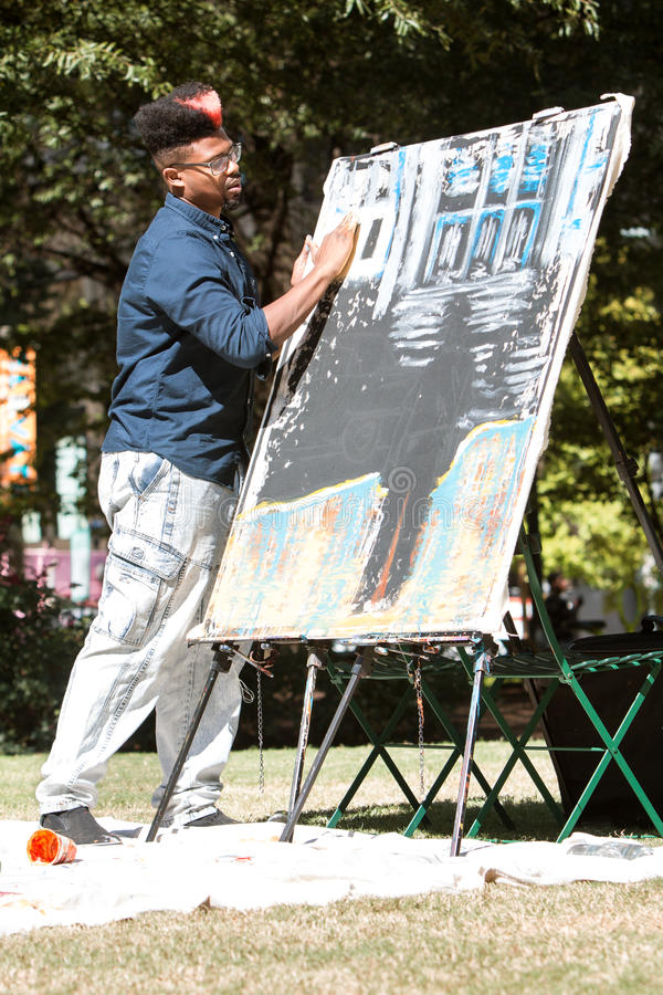 African American Artist Paints With His Fingers At Arts Festival. Atlanta, GA, USA - October 17, 2015: A young African-American artist paints with his fingers in royalty free stock image