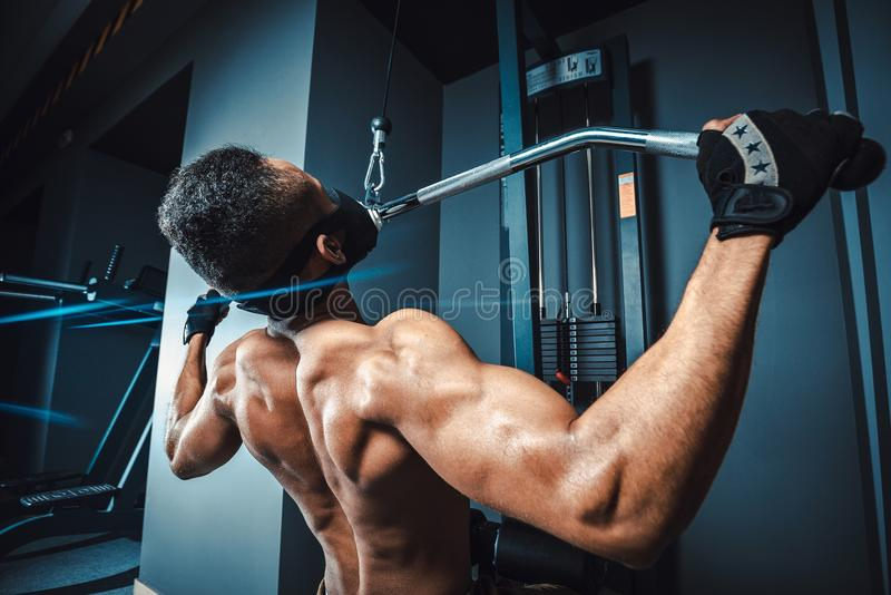 African american athletic man doing exercise in pull down machine back view. black fitness man working out lat pulldown training a royalty free stock photos