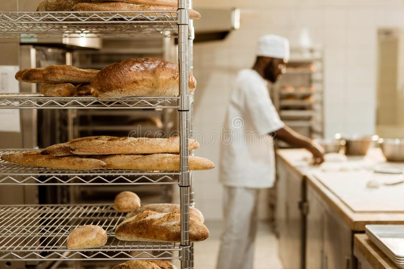african american baker preparing raw dough at workplace with shelves of fresh loaves of bread stock photography