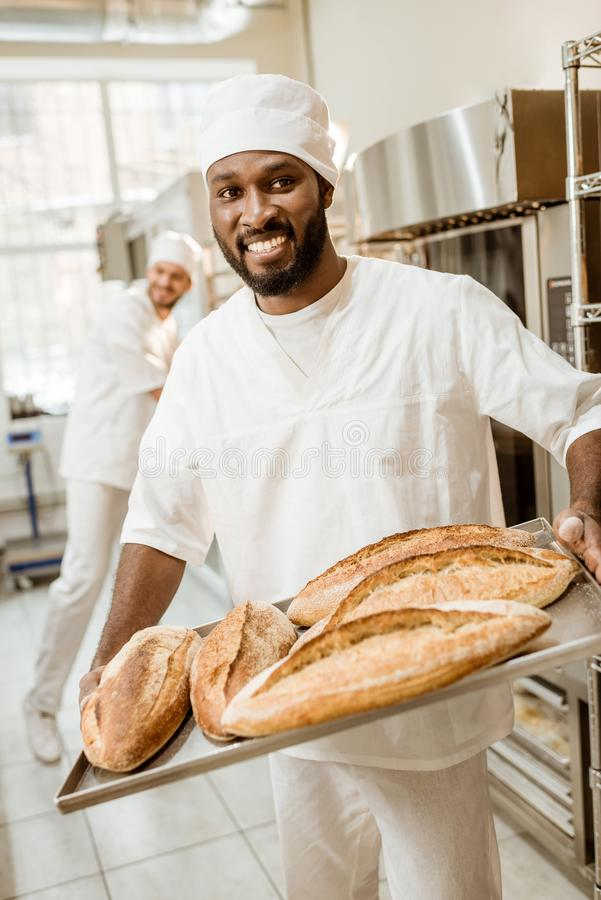 African american baker taking bread loaves from oven. At baking manufacture stock image