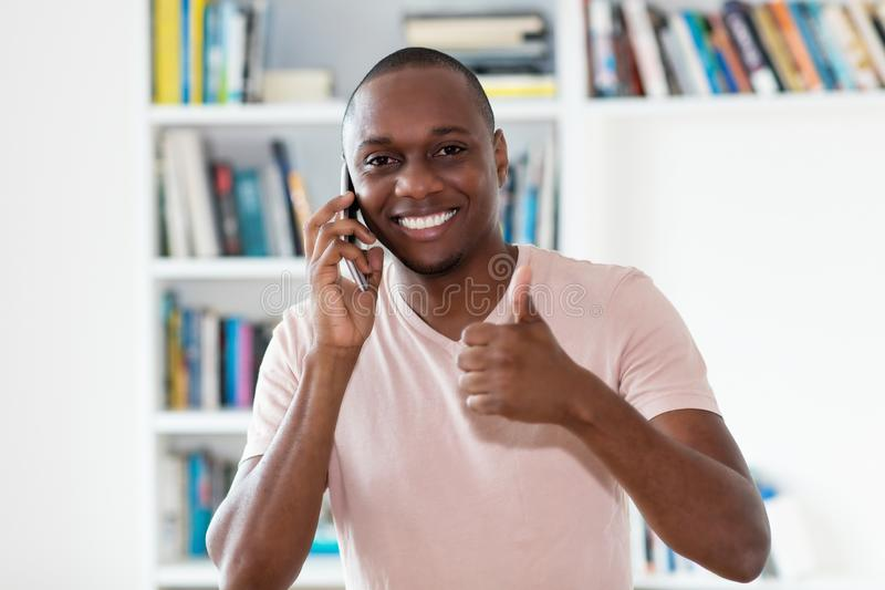 African american bald headed mature man laughing at phone. Indoors at home stock photos
