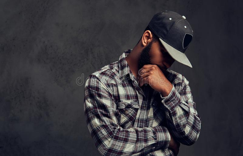African-American bearded guy wearing a checkered shirt and cap royalty free stock photo