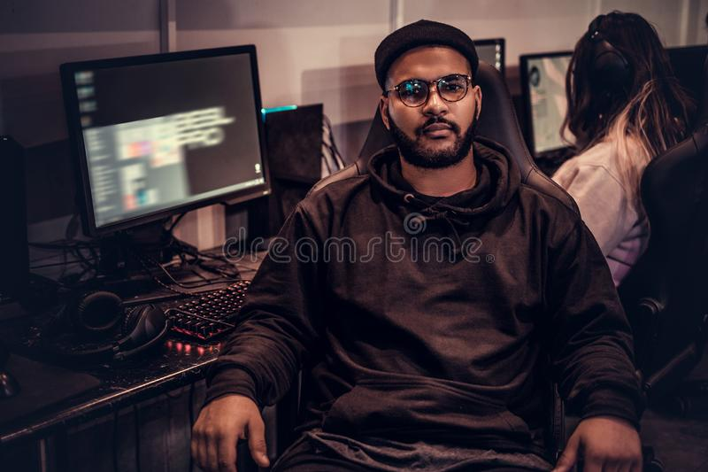 African American bearded guy wearing hoodie and cap sitting on a gamer chair and looking at a camera in a gaming club or stock photo