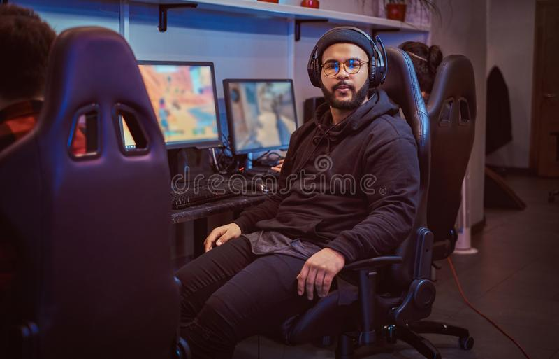 African American bearded guy wearing hoodie and cap sitting on a gamer chair and looking at a camera in a gaming club or. African-American bearded guy wearing royalty free stock photo