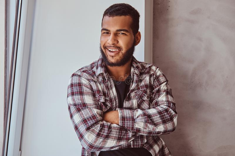 African-American bearded man wearing a checkered shirt with his arms crossed sitting on a window sill. Smiling African-American bearded man wearing a checkered royalty free stock photo