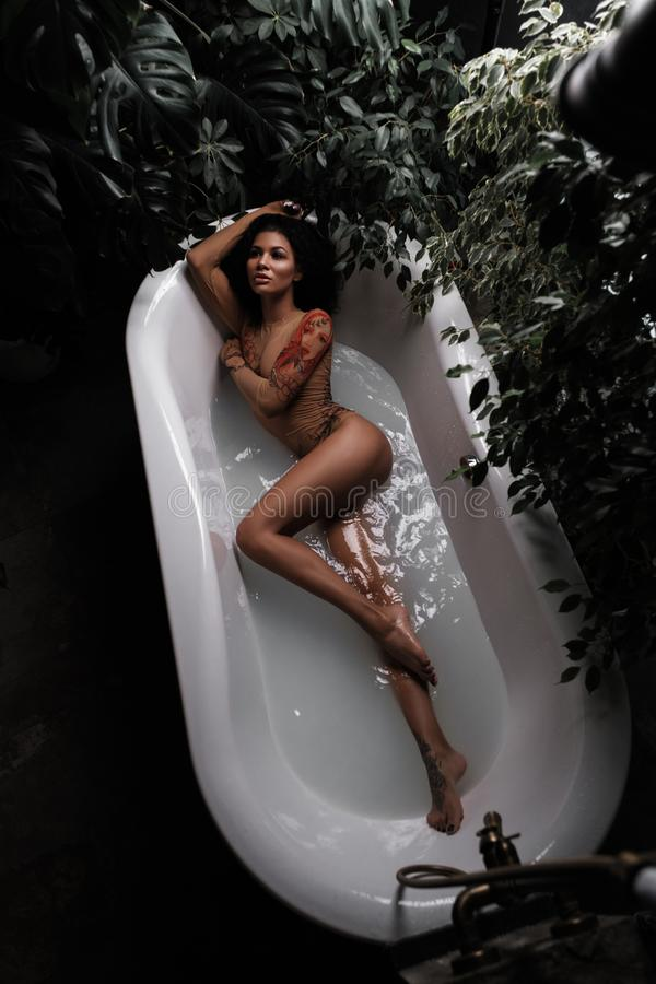 African american beautiful female model with slim gorgeous body is lying and posing in the bath full of water in the jungles stock images