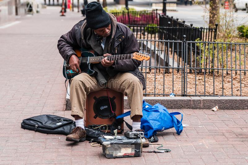 Old man homeless playing guitar begging for money to survive. African American black man plays instrument on the streets hoping for handouts from passersby royalty free stock photography