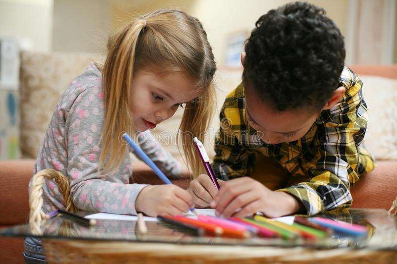 African American boy and Caucasian girl drawing together. Little royalty free stock photos
