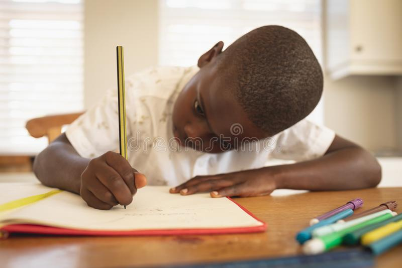 African American boy doing homework on dining table in kitchen. Close-up African American boy doing homework on dining table in kitchen at home royalty free stock photography