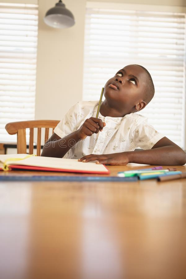 African American boy doing homework on dining table in kitchen royalty free stock image