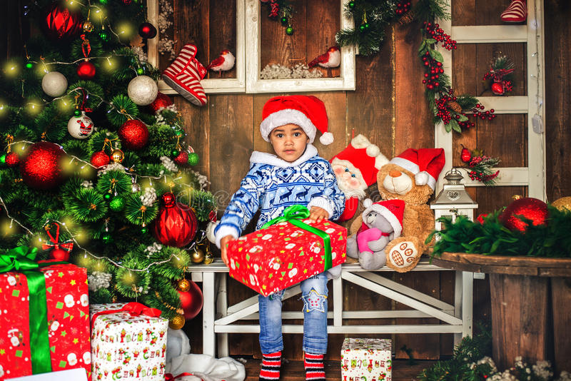 African American boy dressed costume Santa Claus. Near Christmas tree with a gift. Christmas and New Year royalty free stock images